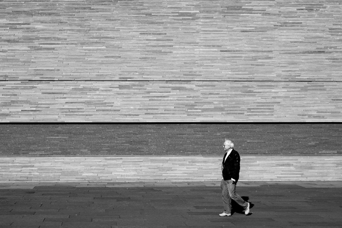 A man walks past a wall.